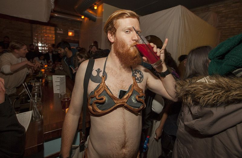 A person with a beard drinking a cocktail while dressed in a bikini from Star Wars.