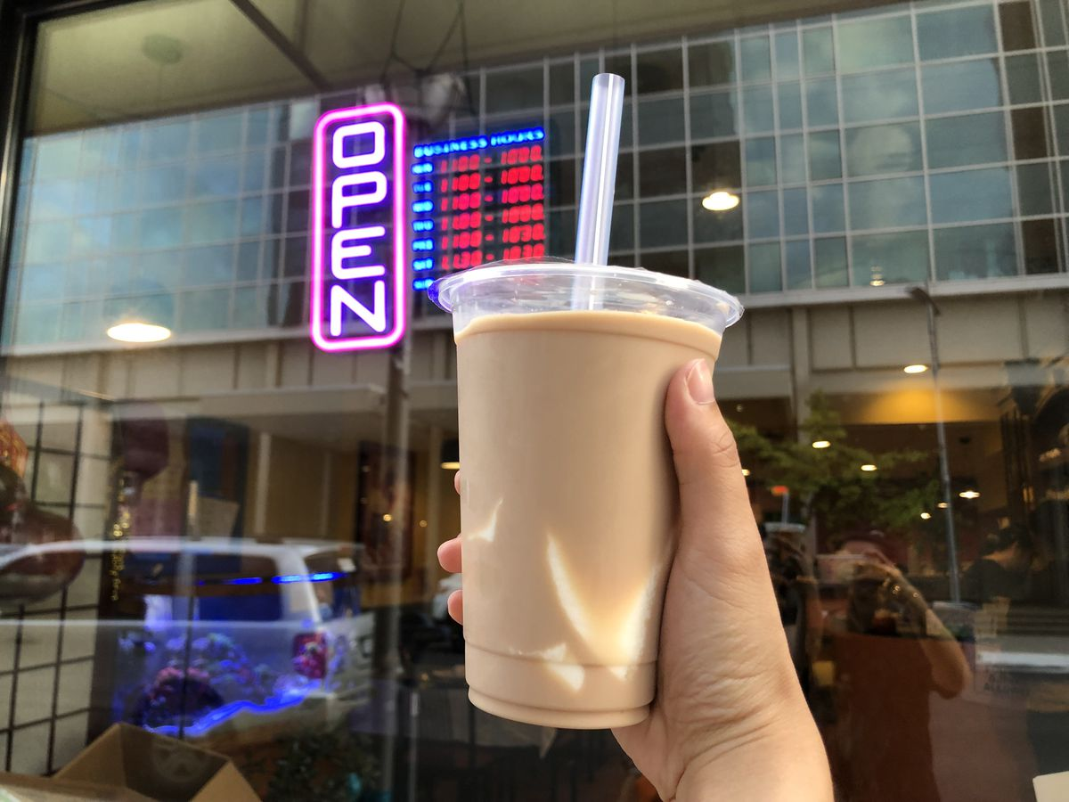 Image of Asian Legend's classic milk tea with tofu topping (center) against the shop's front window, where a neon OPEN sign and list of hours hangs.