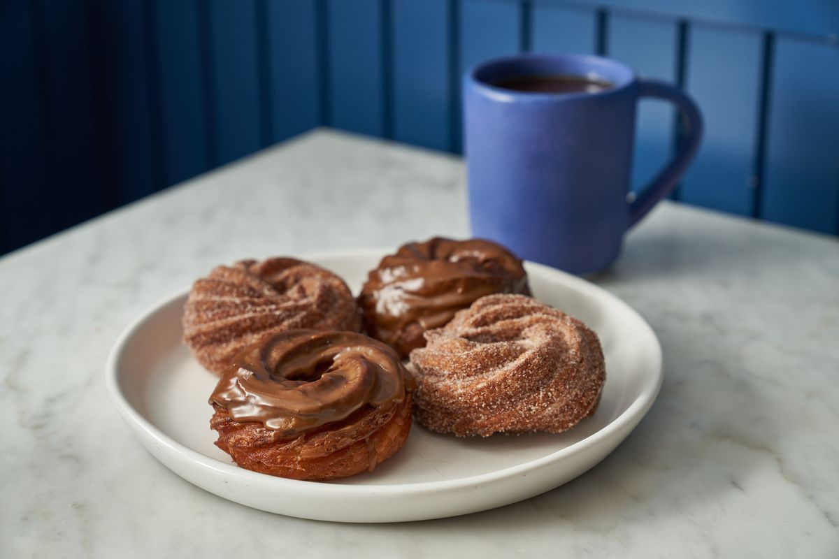 Four dark-colored donuts sit on a plate next to a blue cup of coffee