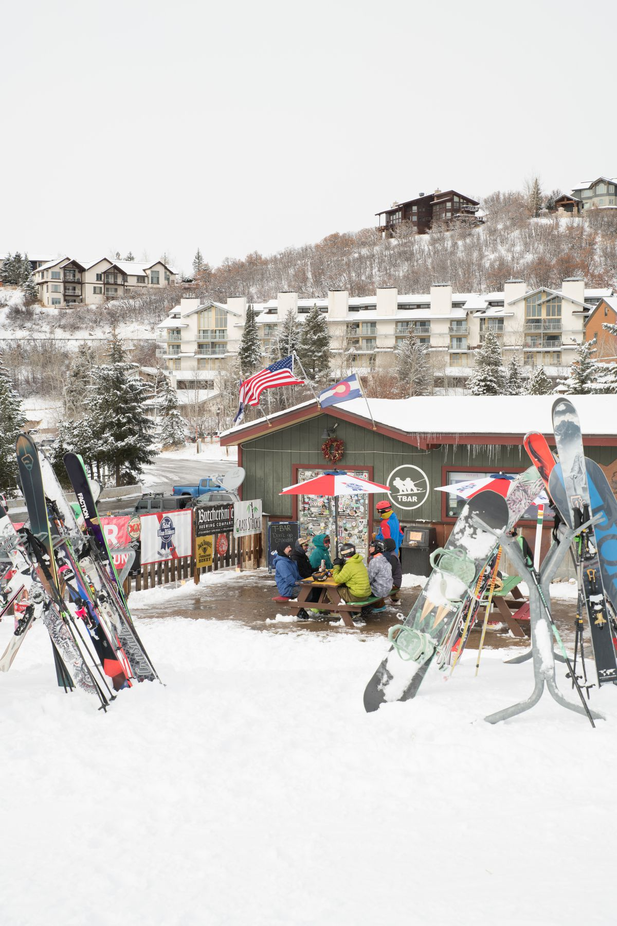 A bar with skis and snowboards resting outside and patrons sitting at an out door table, surrounded by snow.