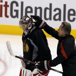 Chicago Blackhawks' Corey Crawford, left, gets his goalie helmet rubbed by assistant coach Mike Kitchen during practice on Wednesday, April 11, 2012, in Glendale, Ariz.  The Blackhawks and the Phoenix Coyotes are scheduled to play Game 1 of an NHL hockey Western Conference quarterfinal series on Thursday.
