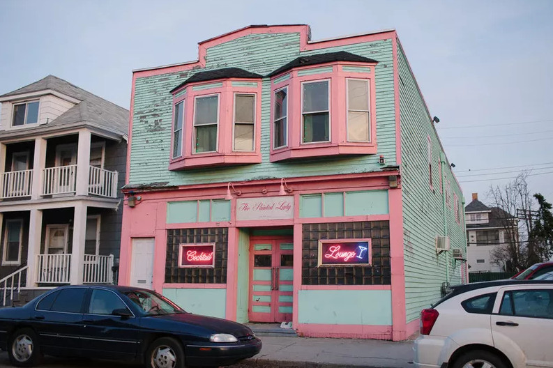 """The Painted Lady is located inside a Victorian-style building with green siding, pink trim, and pink neon signs reading """"cocktail"""" and """"lounge"""" in the windows on either side of the door."""