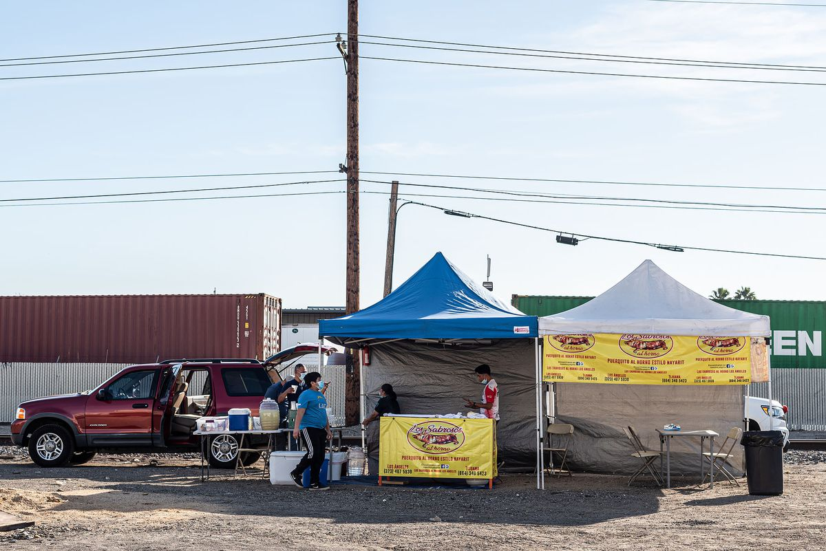 A wide shot of a taco stand in an industrial neighborhood doing suckling pig.