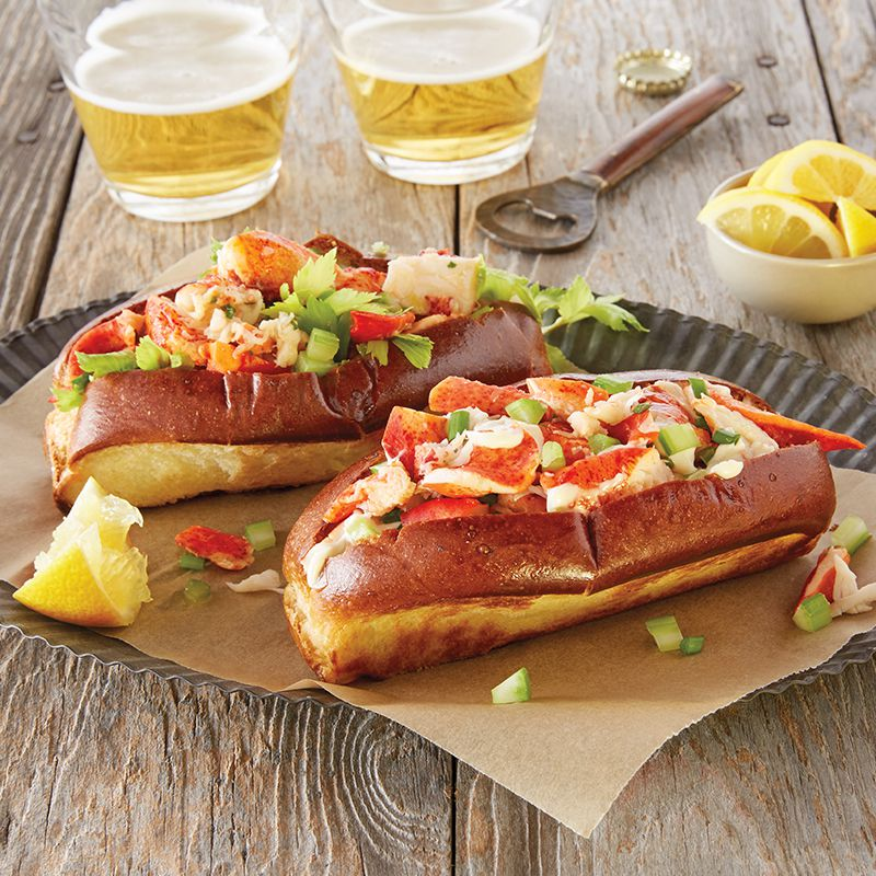 Two lobster rolls on a table accompanied by two glasses of beer and lemons.