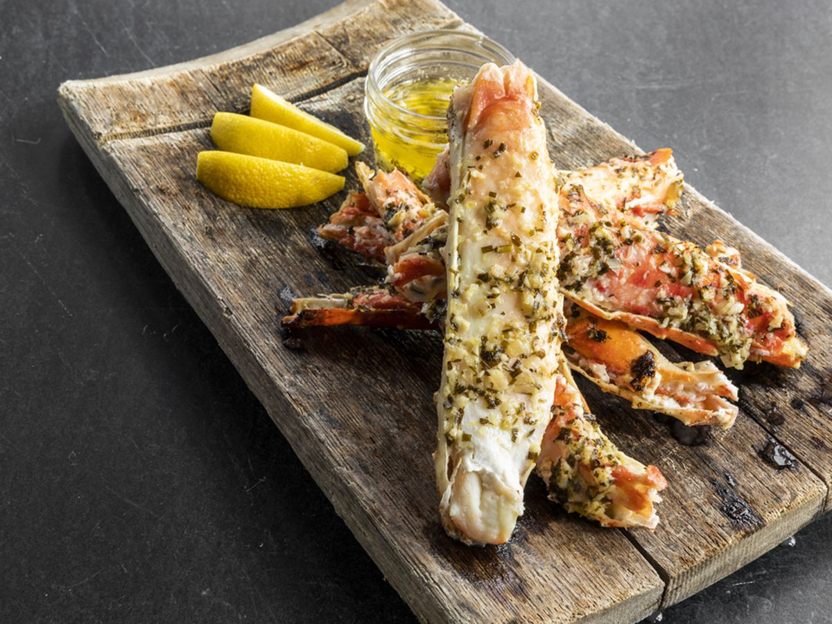 a wooden play topped with king crab legs, lemon wedges and melted butter