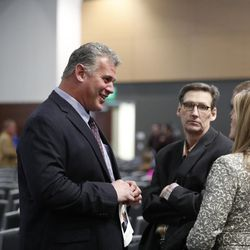Former BYU players Shawn Knight, left, and Dan Plater, center, attend a public memorial service for former Cougar football coach LaVell Edwards at the Provo Convention Center on Friday, Jan. 6, 2017.