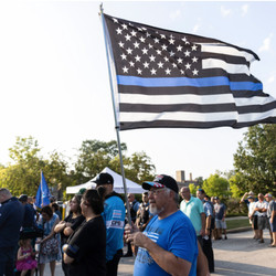 Rich Kielbasa holds a Thin Blue Line flag during a memorial and prayer service for fallen Officer Ella French outside the 22nd District Police Station Wednesday.