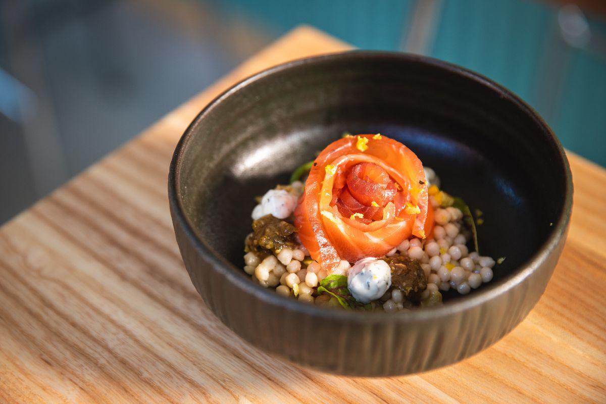 A small pile of cured pink salmon on top of cous cous in a dark brown bowl.