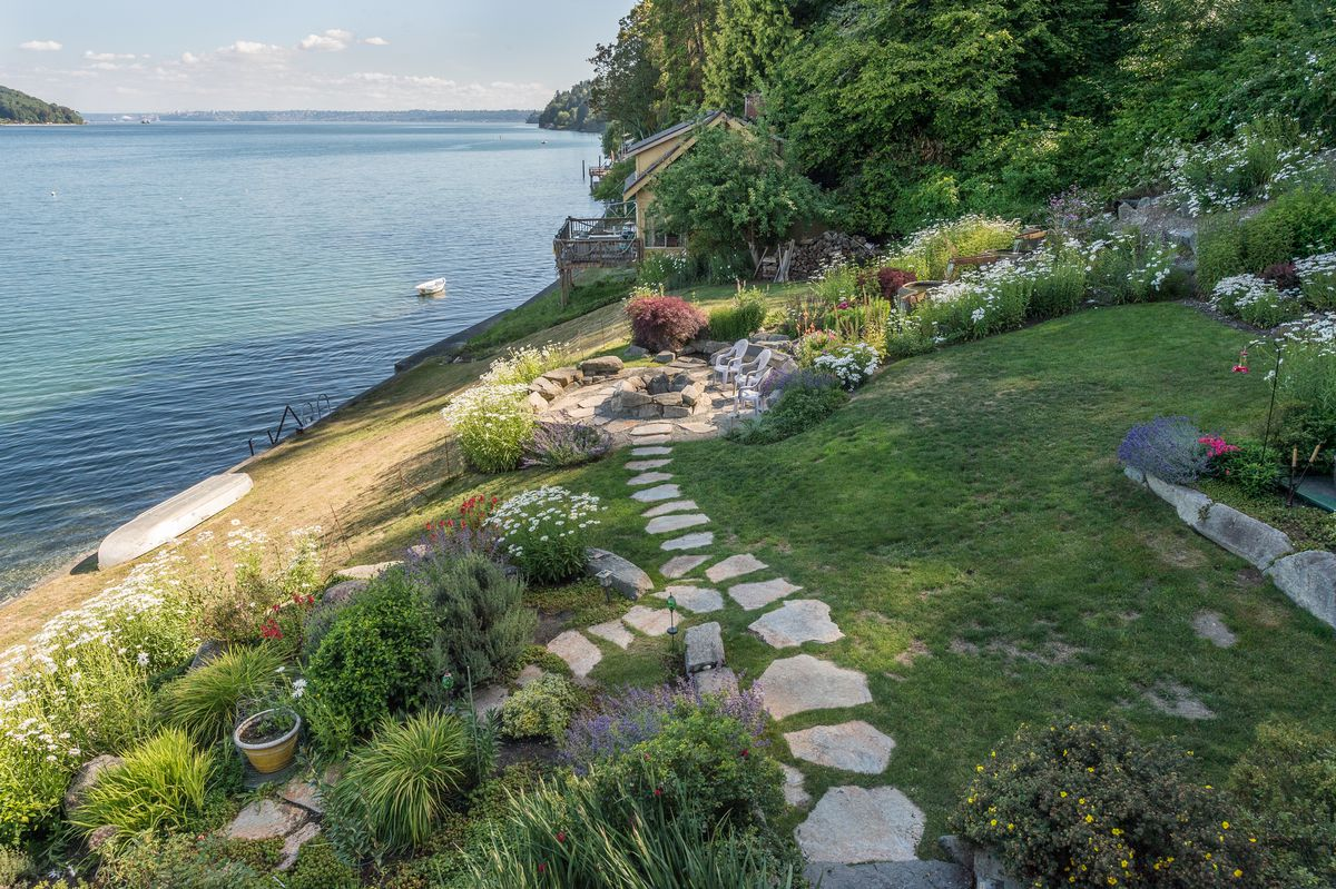 A yard with stone paths and flowerbeds, leading to a stone patio with a stone fire pit in the middle