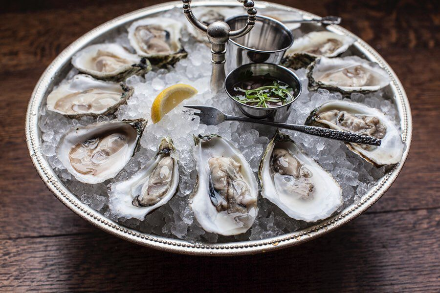 a plate of raw oysters on ice