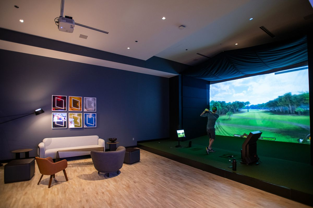 A large room with a golf sim projected on a large screen. There also a lounge area for watching the action.