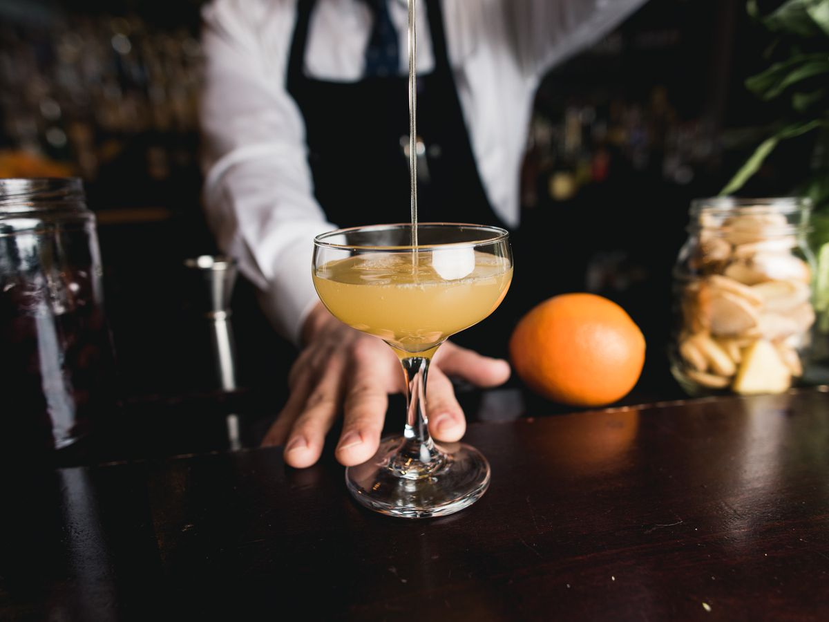 A yellow cocktail is poured into a coup glass.