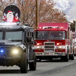 Santa waves as he rides in an armored West Valleypolice vehicle during the department's Giving Tree event in West Valley City on Tuesday, Dec. 22, 2020. The program provided gifts for 159 children from 51 low-income families in the city that were delivered to their homes by police officers. Each child started with a list of needed items and holiday wishes. Santa's helpers from the police department, local businesses and the community then worked hard to fulfill the wishes.