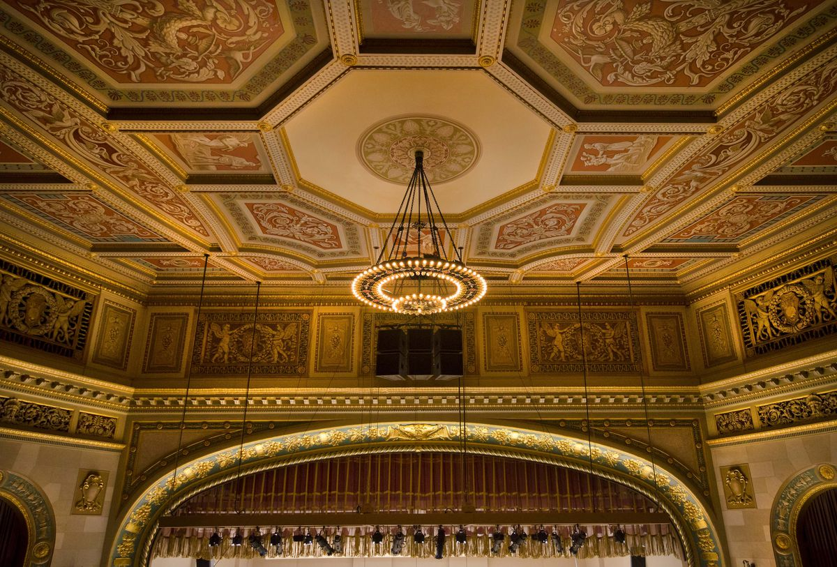 A series of painted panels surround a chandelier on a ceiling. The main stage arch is lit up.