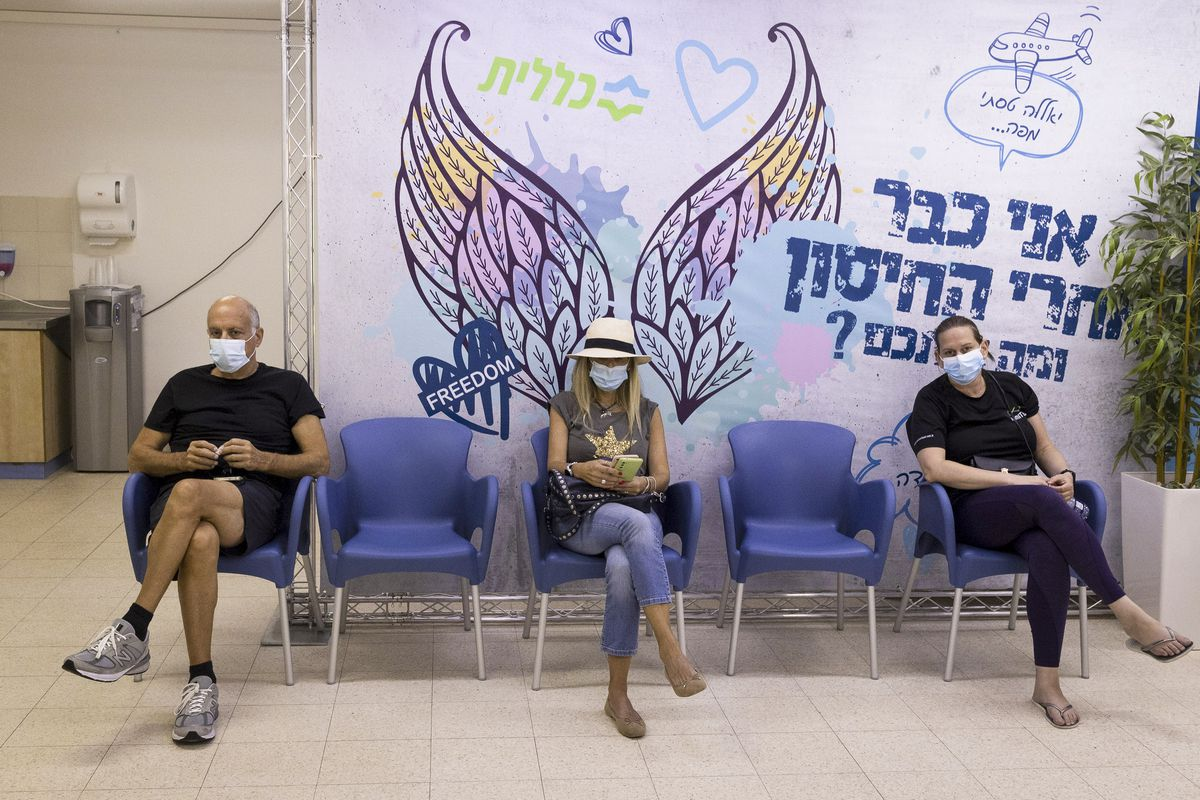 Three masked people sit distanced from one another in a row of five chairs in a medical facility.