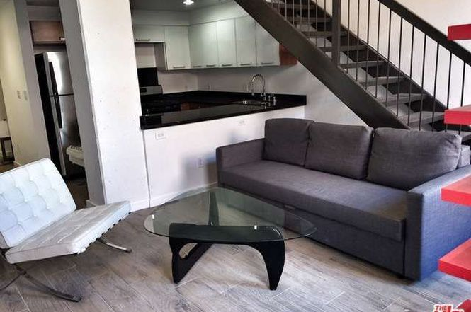 living room with steps to loft space