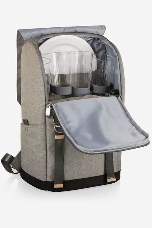 A gray West Elm picnic backpack with plates and cutlery
