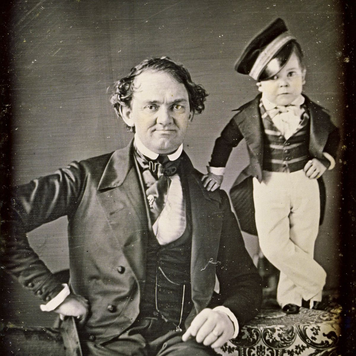 Showman P.T. Barnum leans an elbow on a table, atop which stands performer General Tom Thumb, circa 1850.