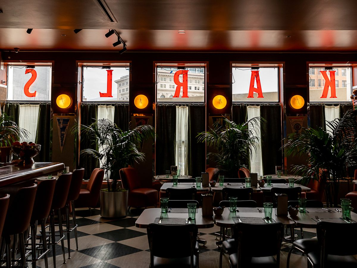 The sign spelling out Karl's is painted in red on the windows above the restaurant's green cafe drapes. The interior of the restaurant features tables and a bar on checker painted wood floors with orange upholstered chairs and lush potted palms.