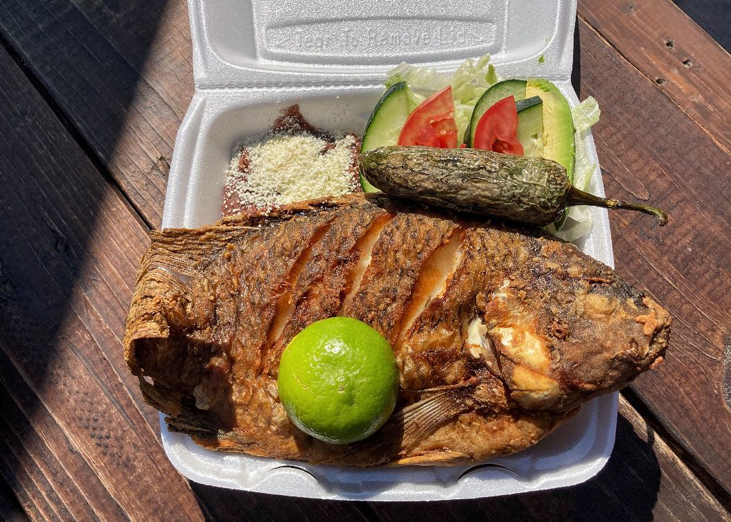 A whole fried fish in a styrofoam container with lime and beans.