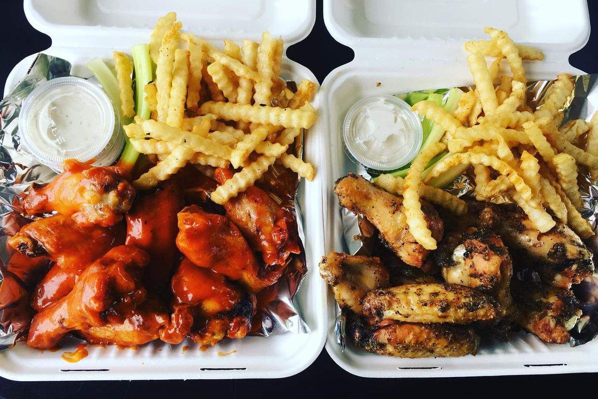 Two takeout containers of Erica's wings sit on a table. The fries next to them are sitting next to a small cup of ranch.
