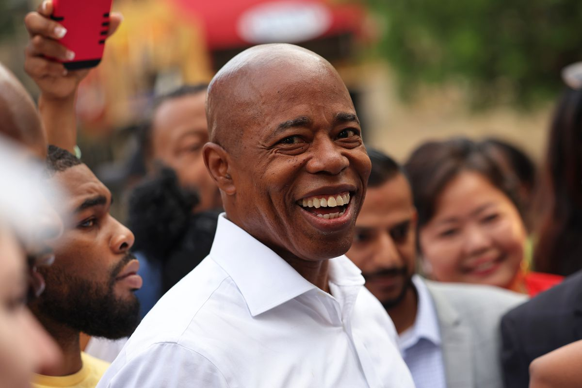 Eric Adams, wearing a white button-up shirt, smiles while surrounded by supporters ahead of the 2021 mayoral primary in New York City.