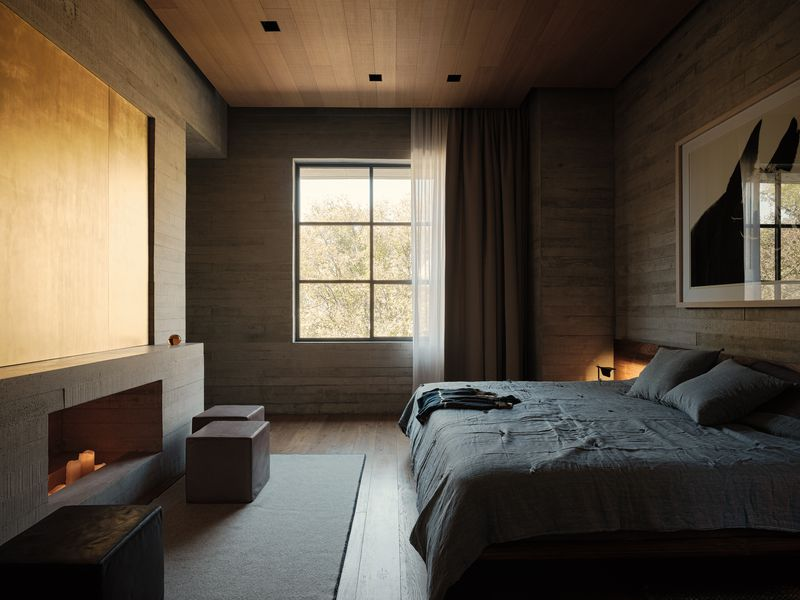 Bedroom with a large gridded window, fireplace, and bed with gray sheets.