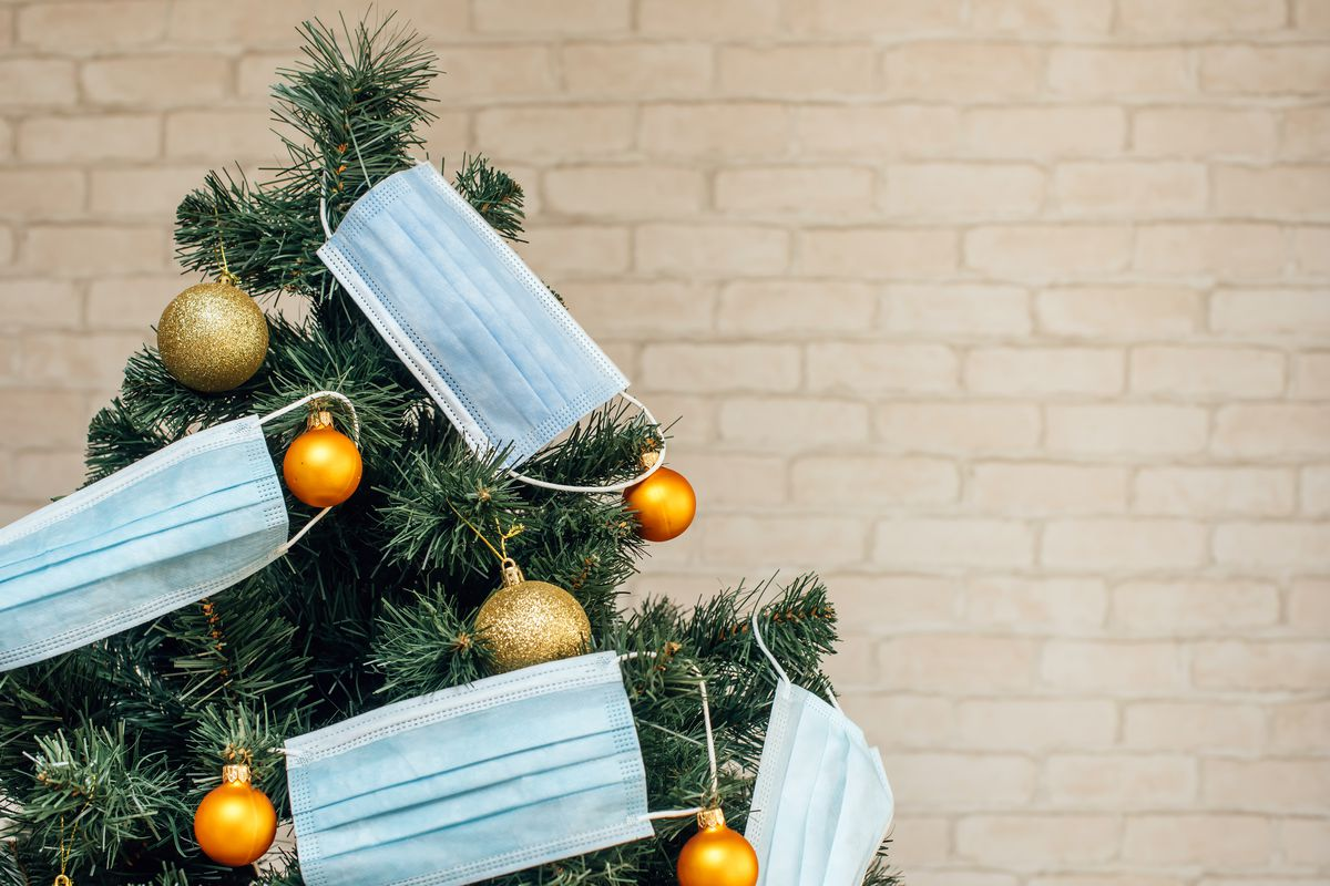 A green Christmas tree adorned with yellow ornaments and light blue surgical masks in front of a cream-colored brick wall