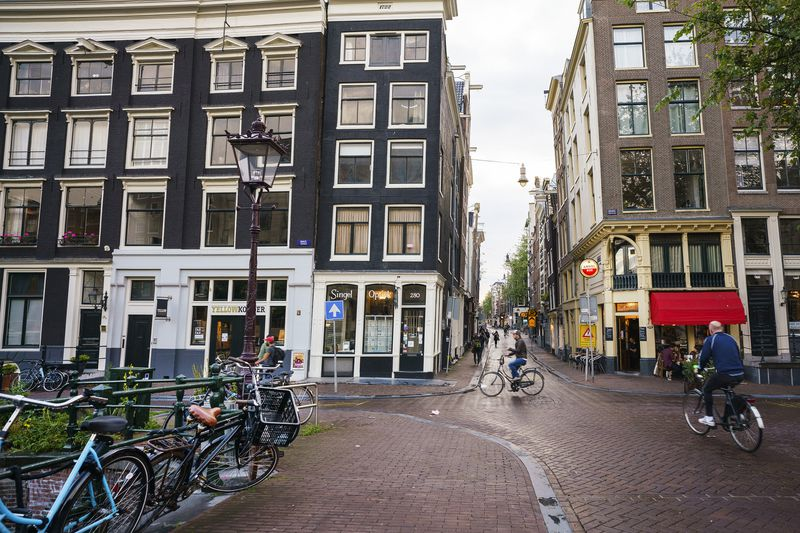 A brick-paved city intersection without cars shows parked bikes and people cycling.