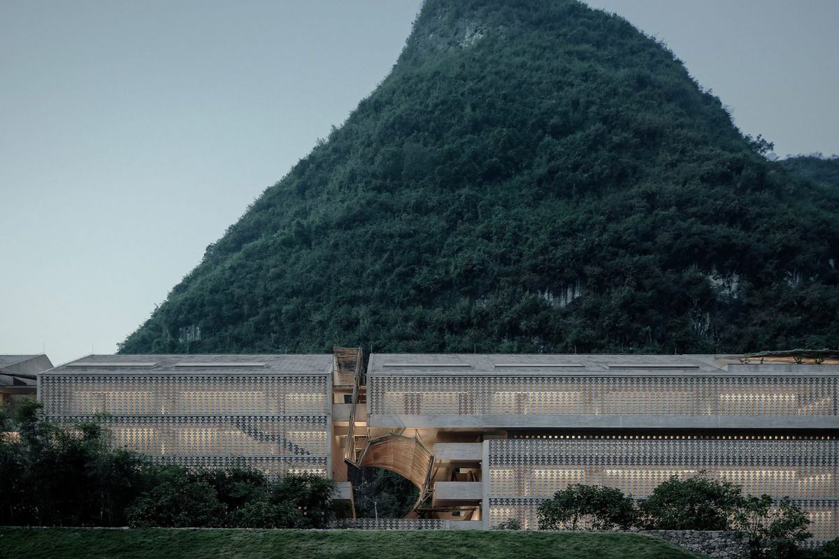 Pointy green mountain rises behind low concrete structure with gabled roof and perforated screen.