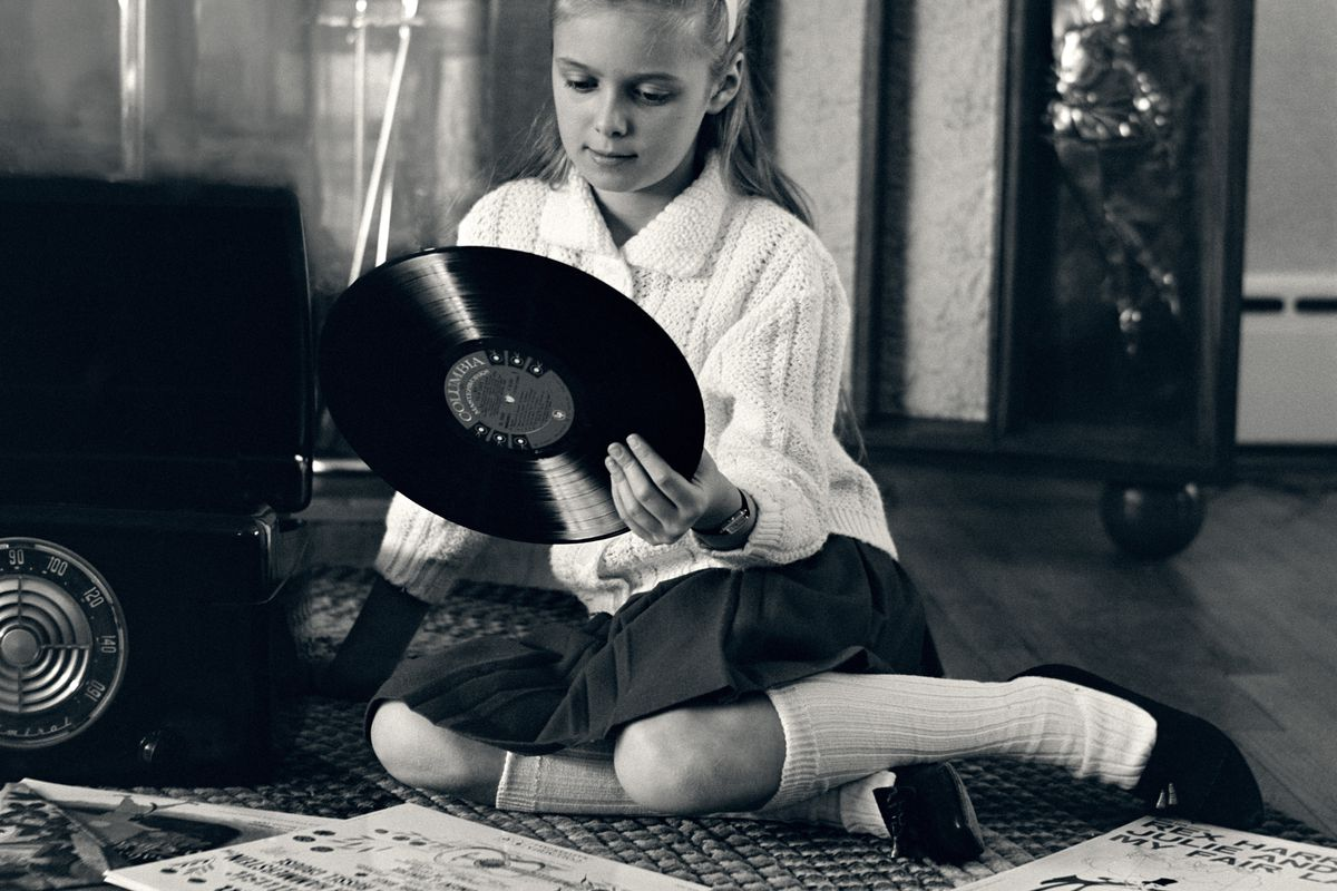 CIRCA 1960s: Teen girl with vinyl records and record player, sitting on floor.