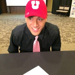 Hunter senior Noah Togiai participates in a ceremonial signing and dons a University of Utah cap, the program to which he committed to play college basketball next year.