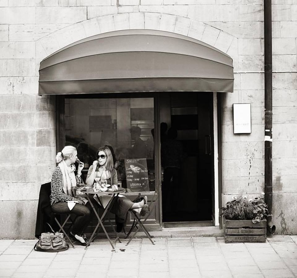 Two women dine at a small patio table outside a stone facade and entrance with an awning