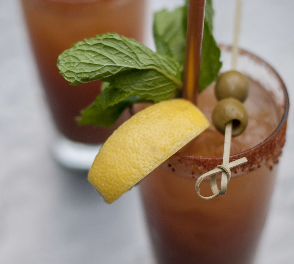 A closeup of a bloody mary in a glass, garnished with lemon, basil, and olives.