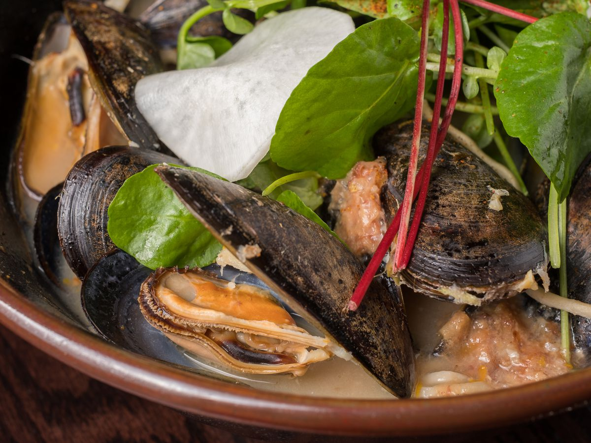 A close up of an earthenware pot filled with broth and mussels