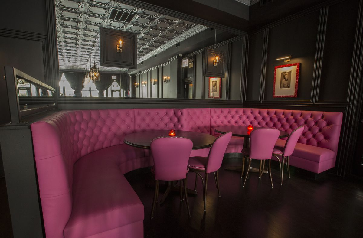 A pink booth with pink leather Victorian style chairs and a back mirror that shows the front of the bar.