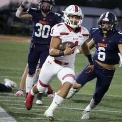 East's quarterback Siona Vailahi runs past Brighton's Nicklaus Hagman (6) and Jace Matheson (30) at Brighton High School in Cottonwood Heights on Thursday, Sept. 22, 2021.