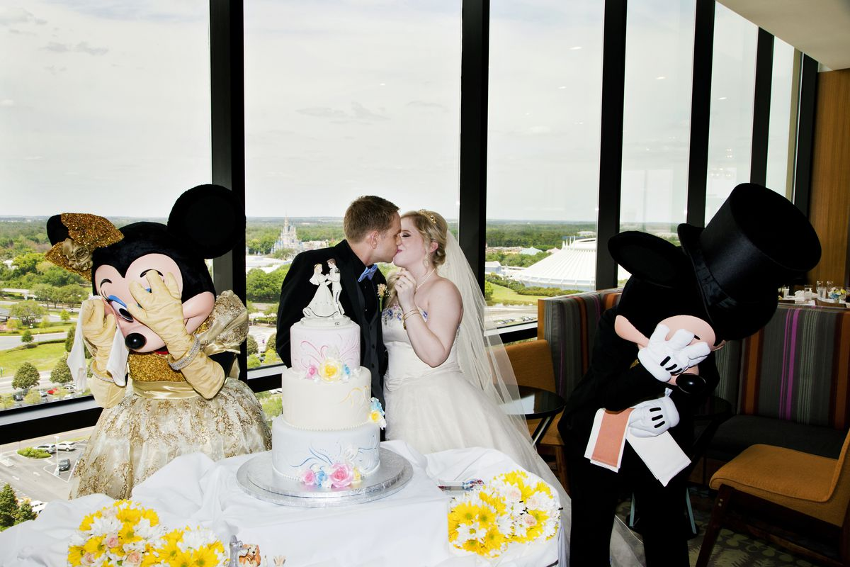 A bride and groom kiss in front of a wedding cake at Disney World, as Mickey and Minnie cover their eyes