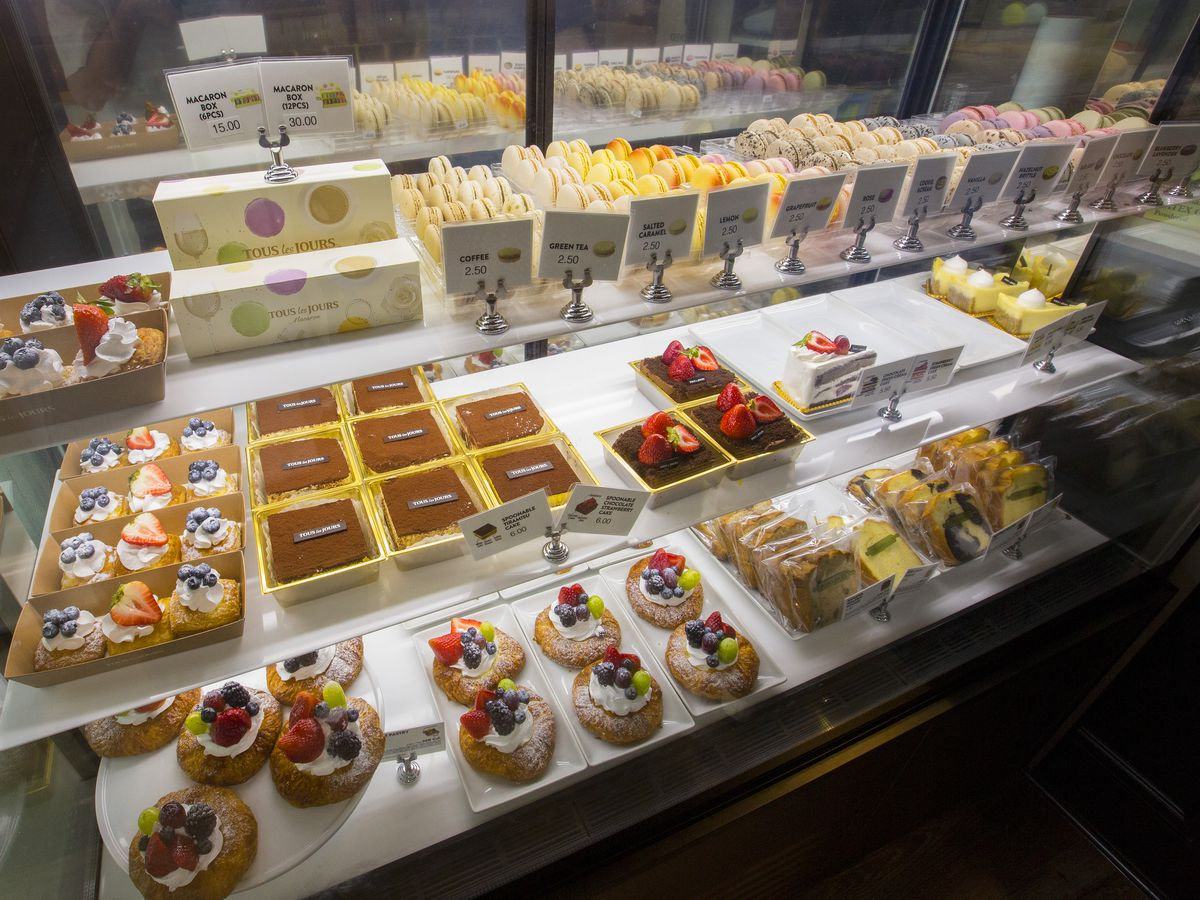 A glass pastry case filled with brightly-colored pastries and desserts.