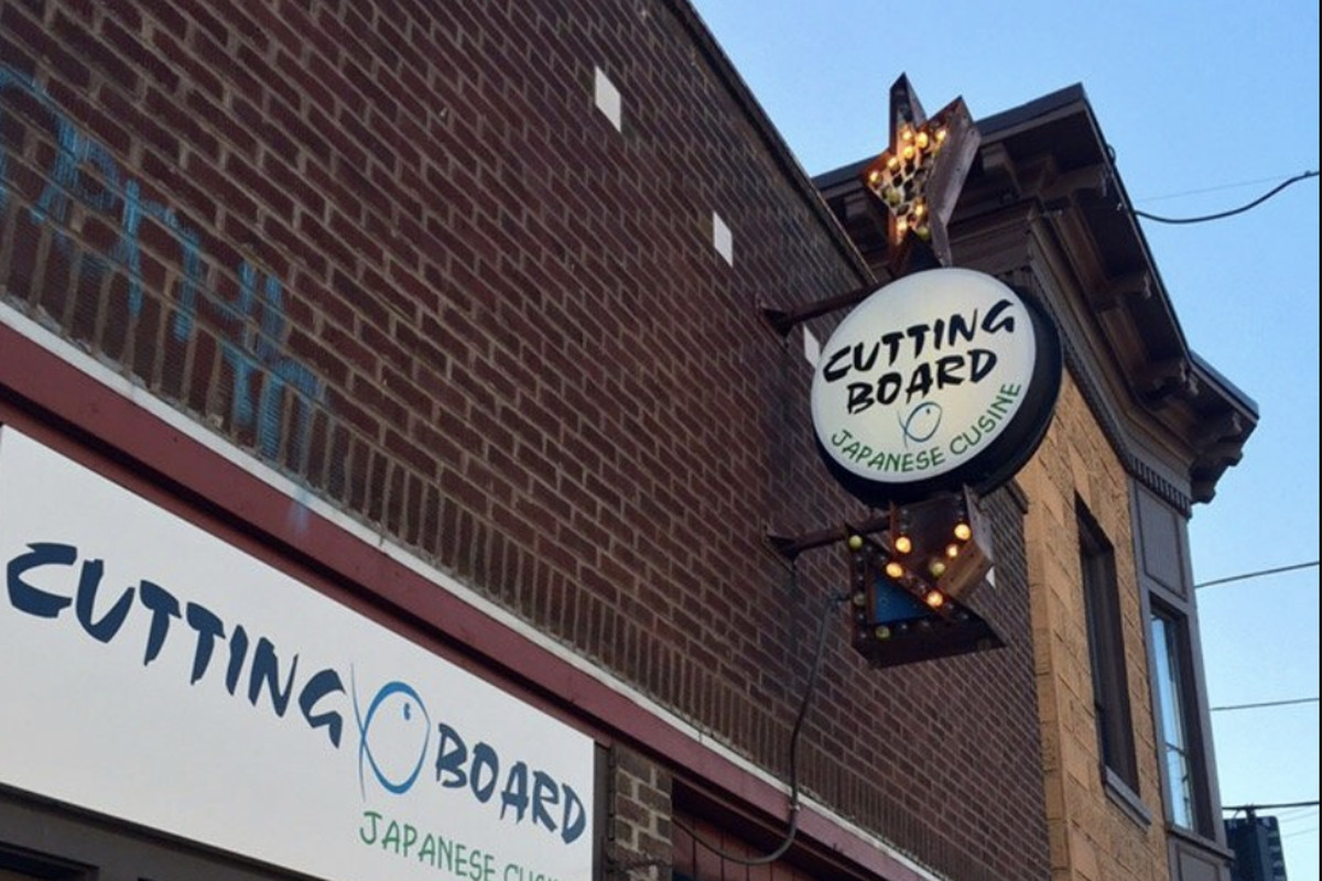 The brick exterior of Cutting Board in Georgetown, displaying the restaurant's signage.