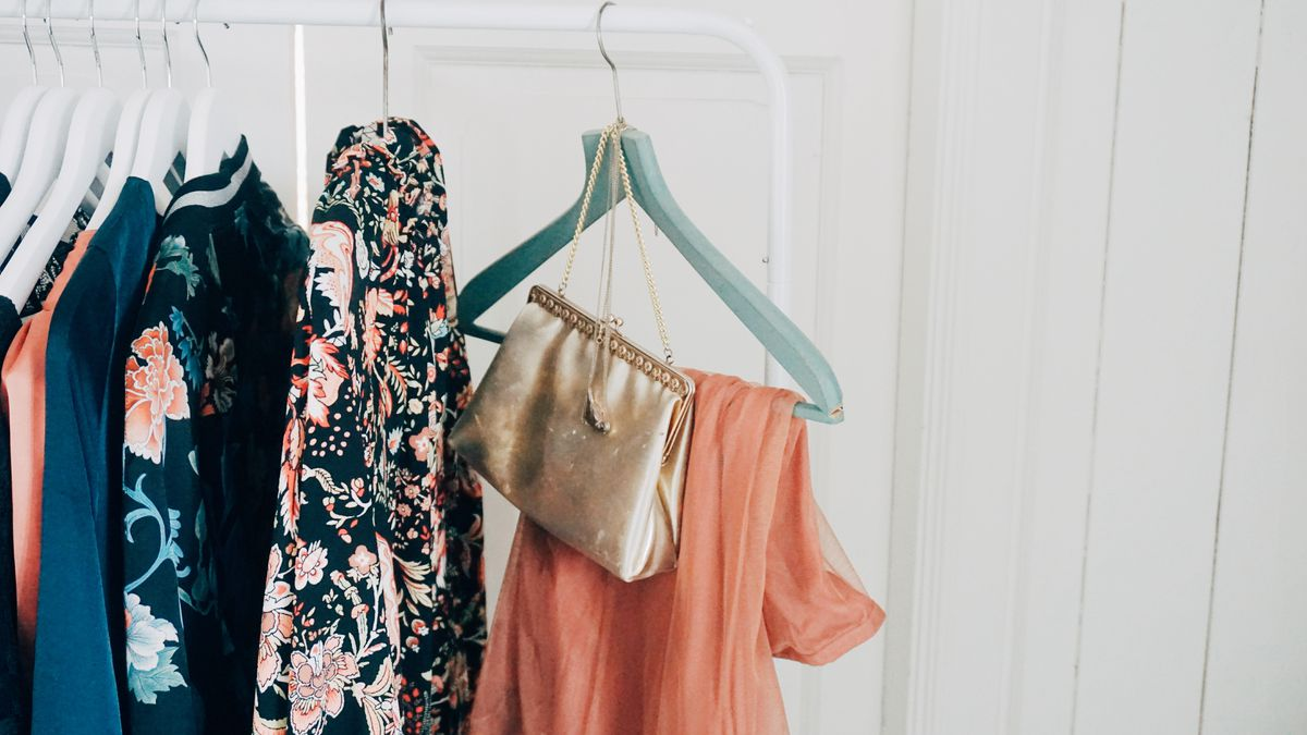Clothes and a small handbag hanging on hangers.