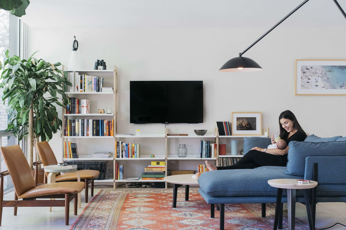 Woman sitting on couch next to shelves