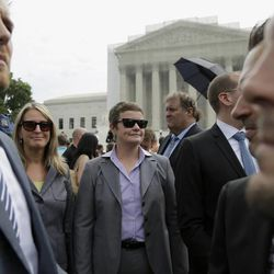 Proposition 8 paintiffs Sandy Stier, second from left, and Kris Perry, third from left, of Berkeley, Calif., who are at the center of the fight for same-sex marriage in California, wait outside for a car as they leave the Supreme Court in Washington, Monday, June 24, 2013. The Supreme Court has 11 cases, including the term's highest profile matters, to resolve before the justices take off for summer vacations, teaching assignments and international travel. The court is meeting Monday for its last scheduled session, but will add days until all the cases are disposed of. (AP Photo/Carolyn Kaster)