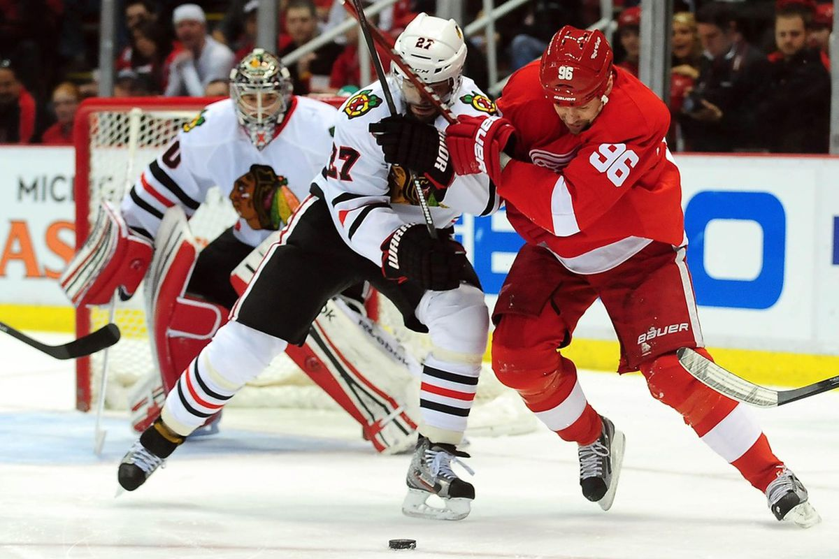 April 7, 2012; Detroit, MI, USA; Detroit Red Wings forward Tomas Holmstrom (96) battles with Chicago Blackhawks forward Bryan Bickell (29) for the puck during the first period at Joe Louis Arena. Mandatory Credit: Andrew Weber-US PRESSWIRE
