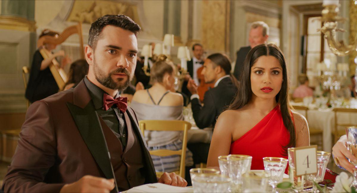 Gross power couple Chaz (Allan Mustafa) and Amanda (Freida Pinto), sitting at a wedding reception table, glare disbelievingly at something offscreen.