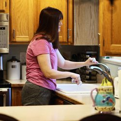 Patricia Abbott Lammi gets a morning milk cup for her daughter Juliet as she works to get her two kids, Luke and Juliet, ready for the day before going off to work on Tuesday, May 2, 2017. Patricia and her husband Phillip work to juggle their work schedules to make things work.