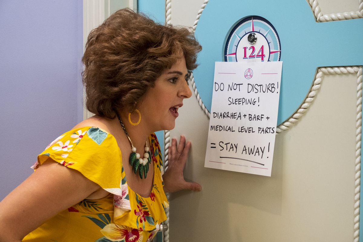 """Annie Mumolo as Barb looking at a sign that says """"Do Not Disturb! Sleeping! Diarrhea + Barf = Medical Level Farts!"""""""