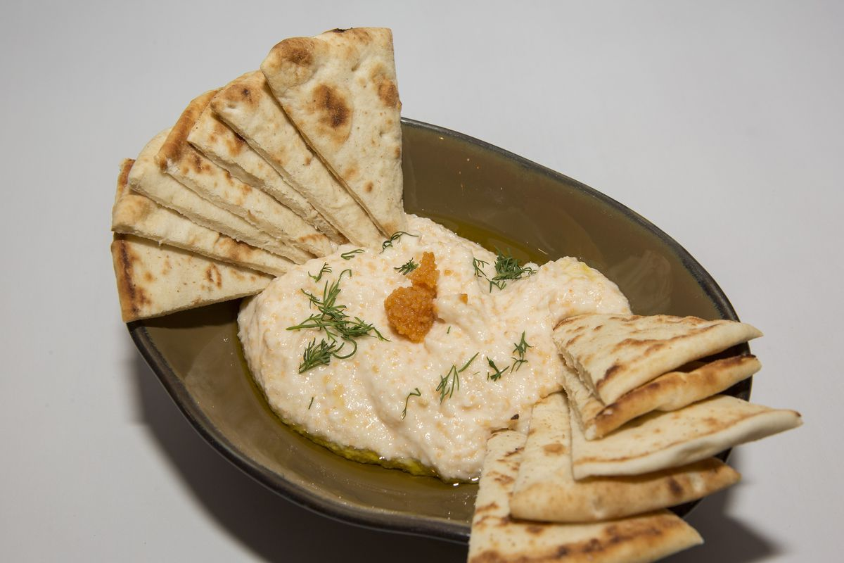 Light-colored Greek spread with pita triangles on a plate.