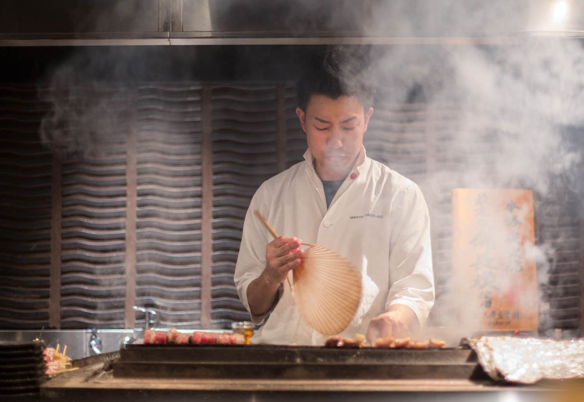 Man cooking skewers over smoking grill.
