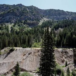 Wood and stone structures and a large pile of mine tailings, the waste rock left over from mining, remain at the site of the former Cardiff Mine in Mill D South Fork of Big Cottonwood Canyon on Wednesday, Aug. 12, 2020. Erosion from spring runoff can be seen along the side of the tailings pile.